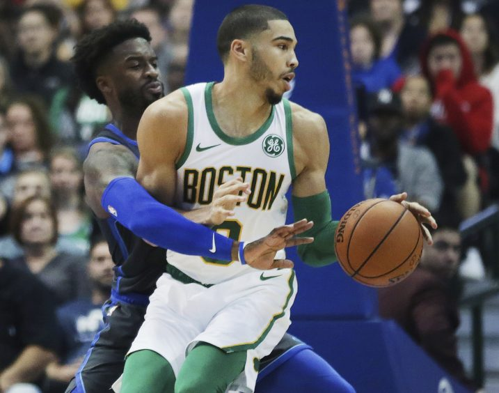 Boston forward Jayson Tatum attempts to move the ball while defended by Dallas guard Wesley Matthews during Saturday's game in Dallas.