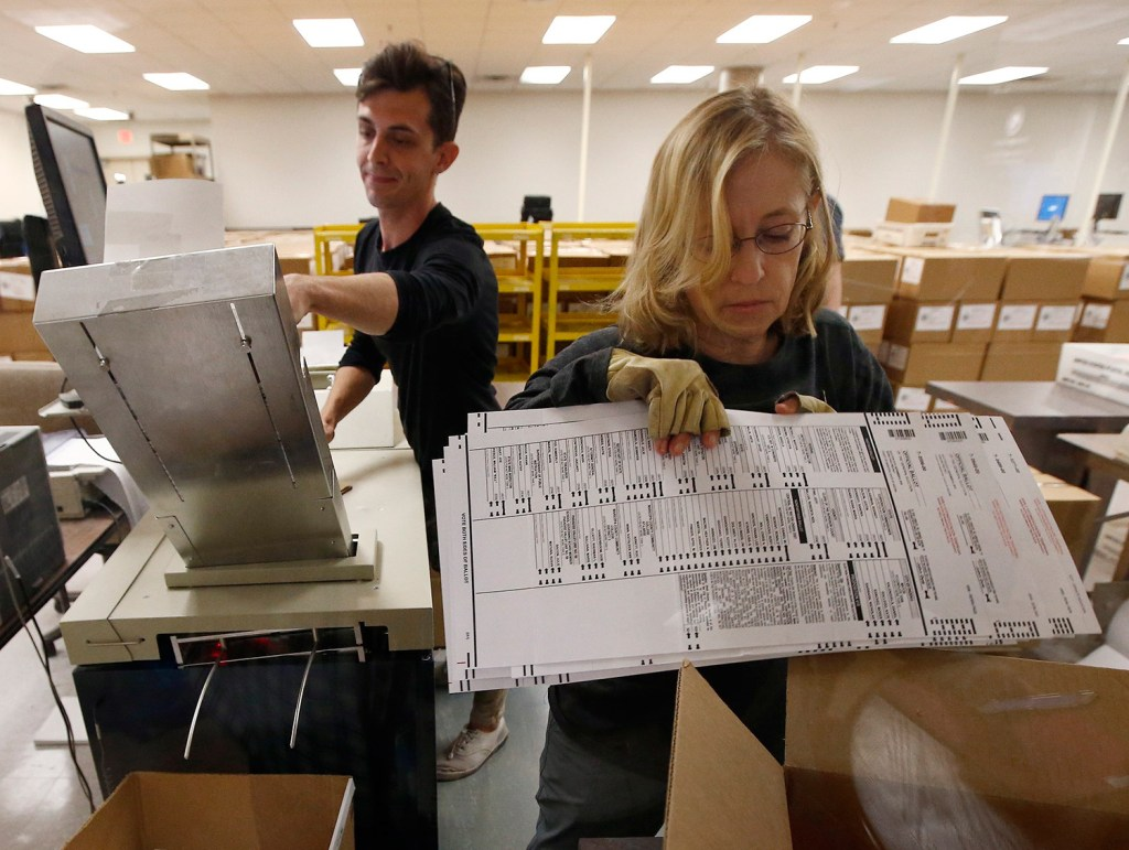 Workers organize ballots at the Maricopa County Recorder's Office in Phoenix on Thursday. By Friday night, one percentage point separated the candidates in the Senate race between Democrat Kyrsten Sinema and Republican Martha McSally.