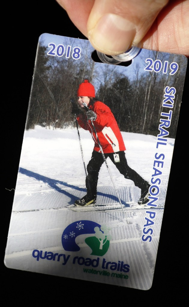 Left: Thomas Klepach, a volunteer at Quarry Hill Trails, shows his season pass for the ski trails. Below: Rosalea Kimball of Readfield skates uphill at Quarry Road Trails.