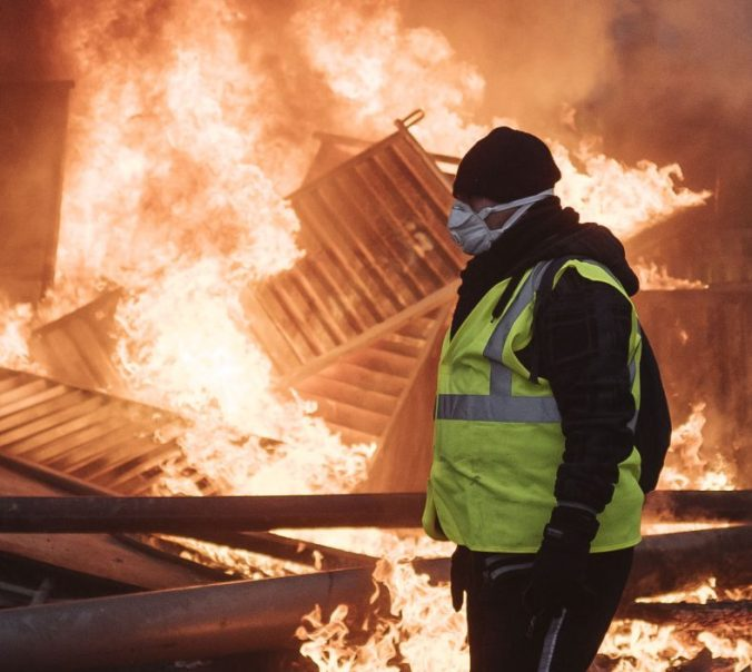 A protester walks past a burning barricade near the Arc de Triomphe during a demonstration Saturday in Paris. It was the third straight weekend of clashes.