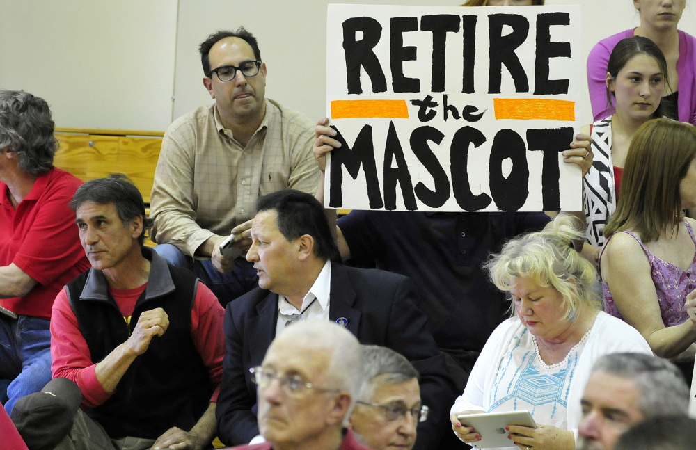Mark Roman holds a sign protesting use of the name Indian for SAD 54 sports teams during a forum in 2015 in Skowhegan. At far left is former chief of the Penobscot tribe Barry Dana, of Solon.
