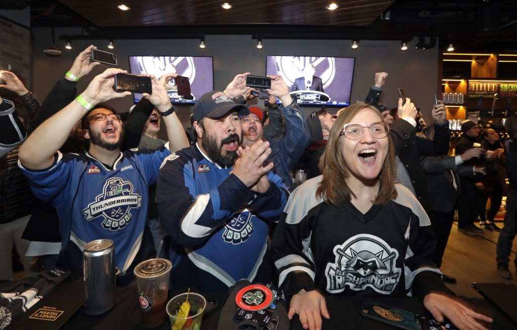 Ryan Kelly, left, Otto Rogers and Rebecca Moloney cheer the announcement of a new NHL team in Seattle at a celebratory party Tuesday. The NHL Board of Governors unanimously approved adding the league's 32nd franchise.