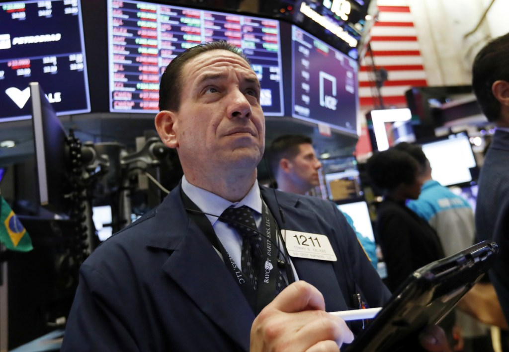 Tommy Kalikas works on the New York Stock Exchange floor Thursday. Signs that the Federal Reserve may back off raising interest rates helped propel stocks back up.
