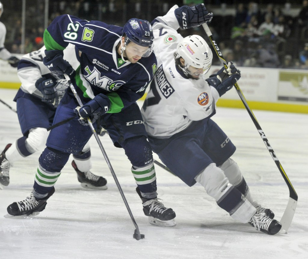 Mariners defenseman Garrett Cecere pulls the puck away from Worcester's Tyler Barnes during a rush up ice leading to Maine's first-period goal Sunday.