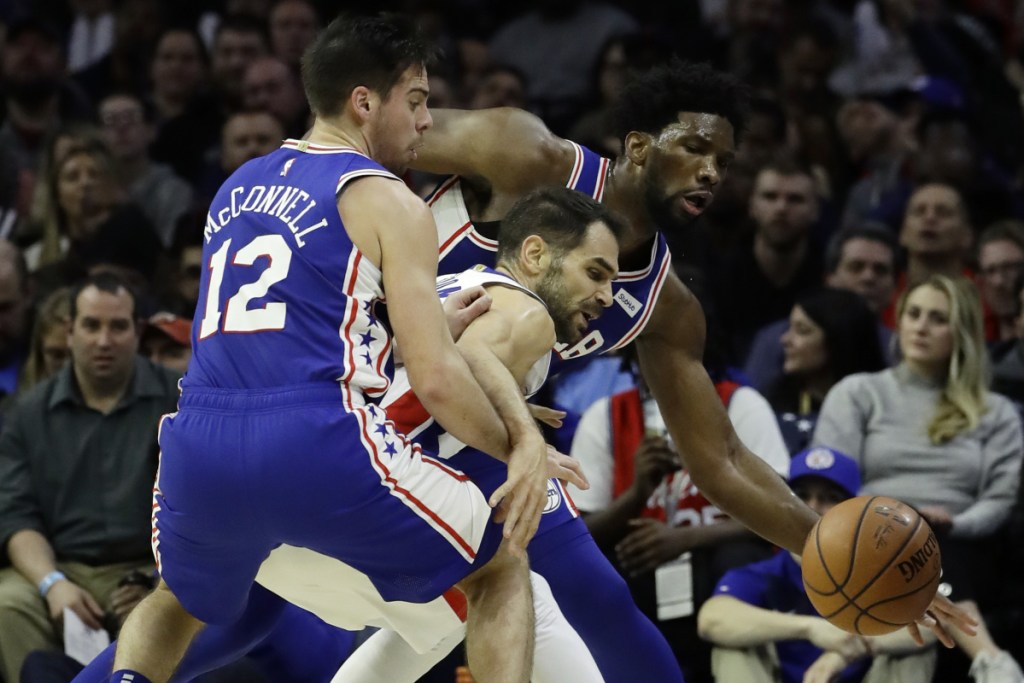 Detroit's Jose Calderon, center, battles for a loose ball against Philadelphia's Joel Embiid, right, and T.J. McConnell during the second half of the 76ers' 117-111 win Monday in Philadelphia.
