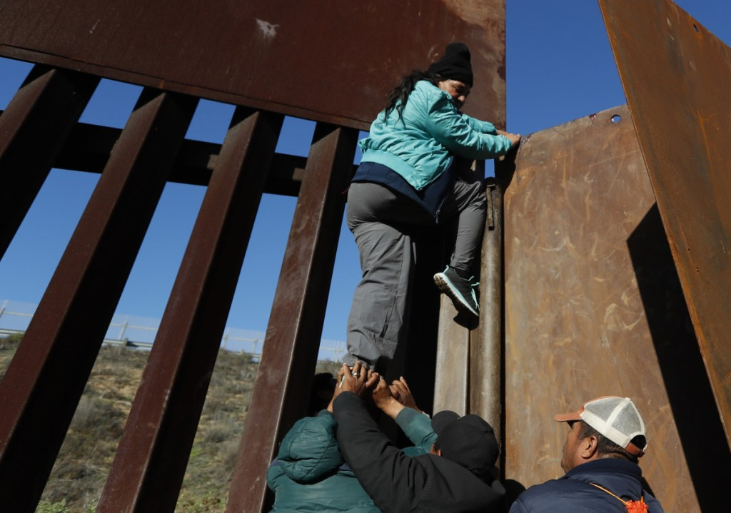 Honduran migrants help a woman scale a section of the border wall to San Diego on Wednesday so she could turn herself in and apply for asylum. President Trump's border wall proposal has led to a stalemate in budget negotiations.