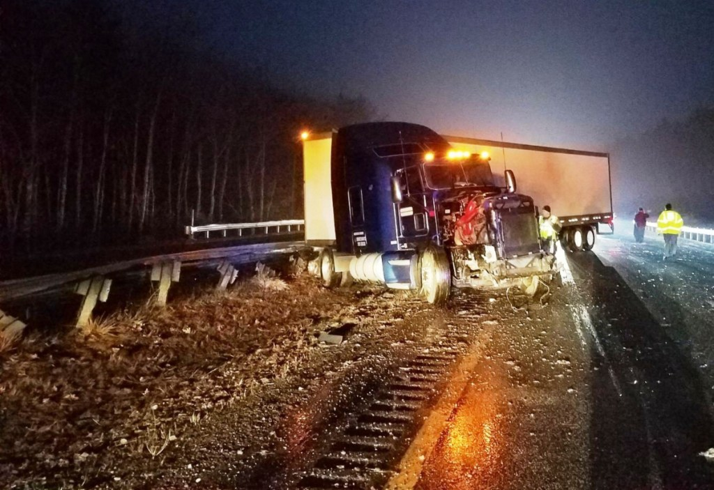 This tractor-trailer truck hit a parked Maine State Police cruiser on the Maine Turnpike early Friday, injuring Trooper John Davis, police said.