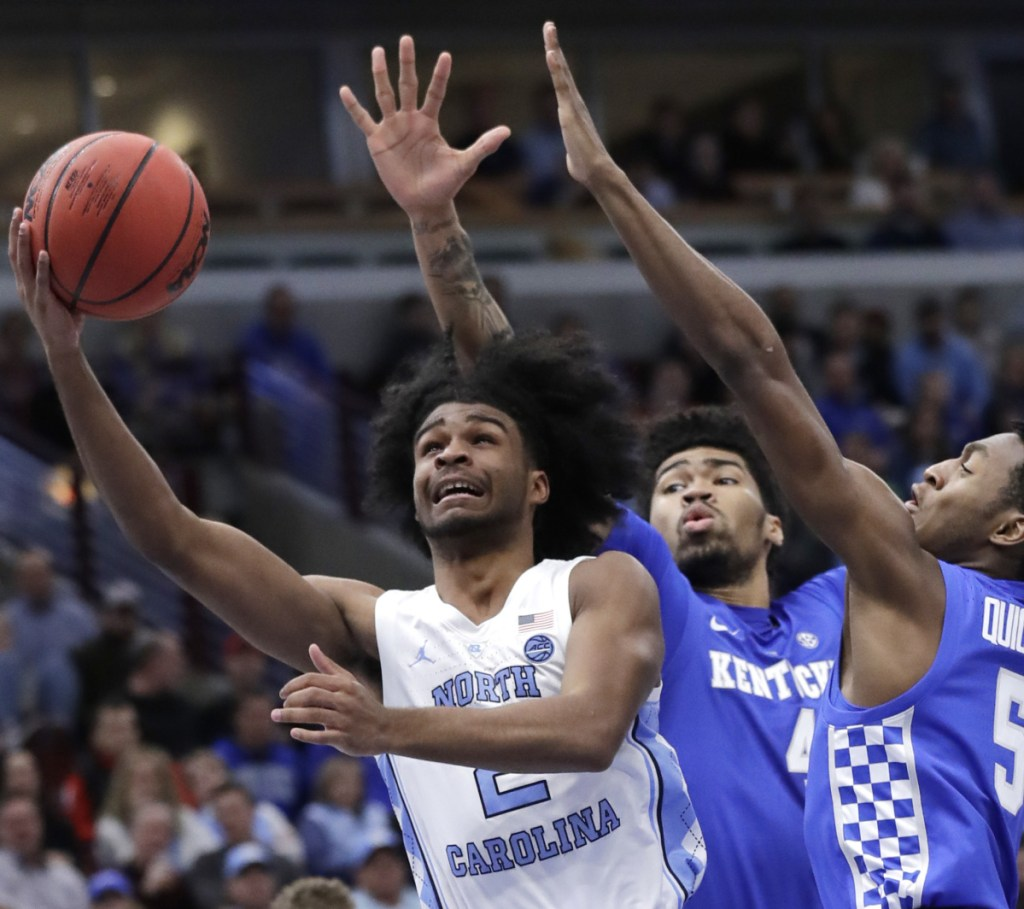 North Carolina guard Coby White, left, takes a shot while being defended by Kentucky forward Nick Richards, center, and guard Immanuel Quickley during the Wildcats' 80-72 victory on Saturday in Chicago.