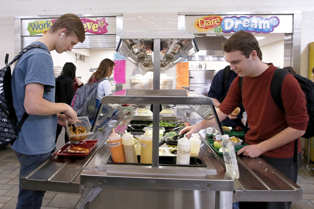 Sophomores Morrison Doucette, left, and Ethan Russell load up at the salad bar at Bonny Eagle High School. The Trump administration may have rescinded nutrition requirements, but some districts are keeping it old school.