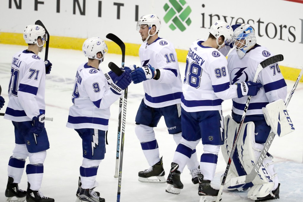 Tampa Bay Lightning goaltender Louis Domingue, far right, celebrates with defenseman Mikhail Sergachev (98) and teammates after the Lightning beat the Devils 5-1 on Monday in Newark, New Jersey.