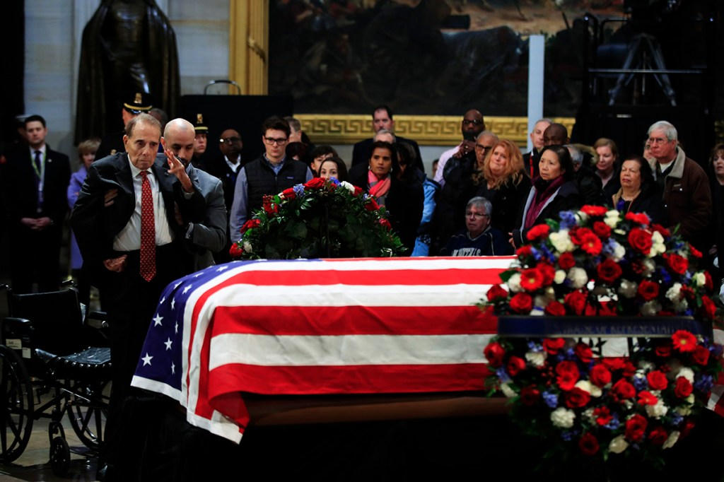 Former Sen. Bob Dole salutes the flag-draped casket containing the remains of former President George H.W. Bush at the U.S. Capitol in Washington on Tuesday.