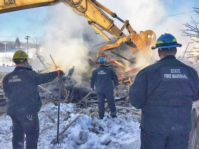 State fire officials search the rubble of house destroyed by fire in Millinocket on Thursday.