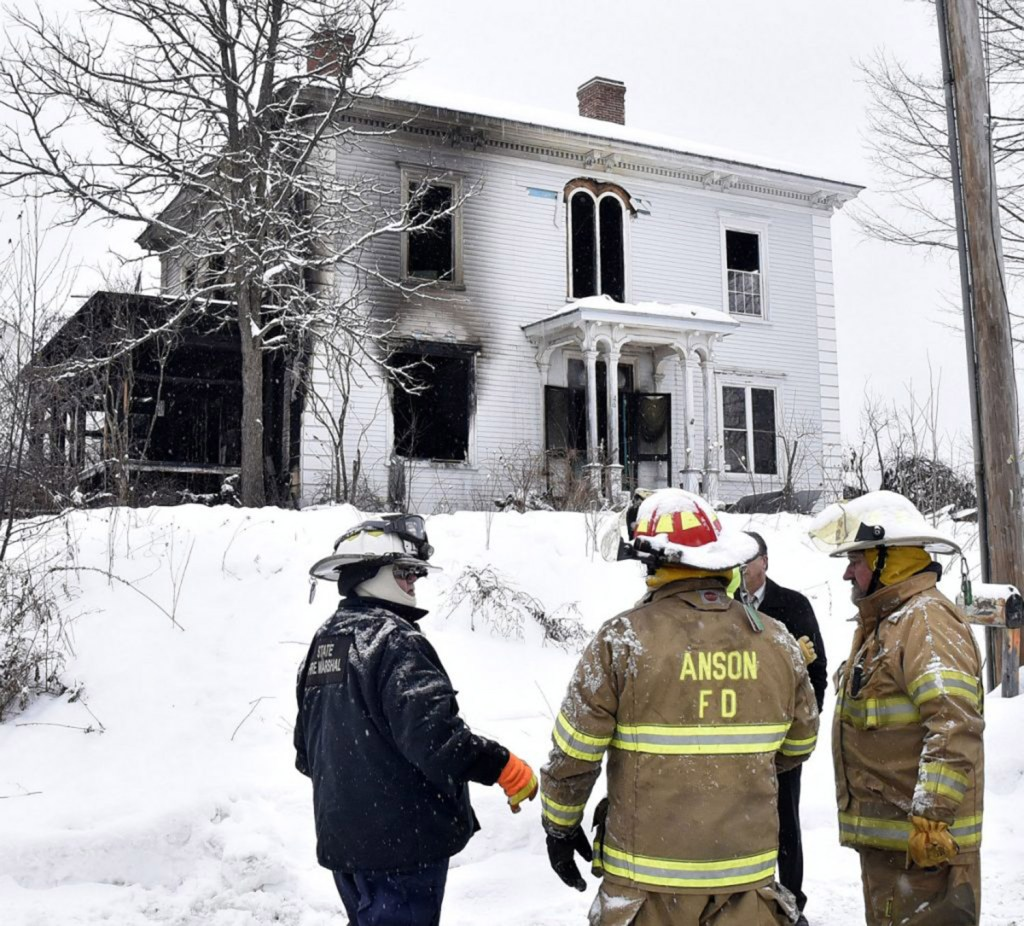 Ken Macmaster, left, of the State Fire Marshal's Office, speaks with firefighters outside the home at 46 North Main St. in North Anson after fire killed a man there and caused serious damage on Thursday.