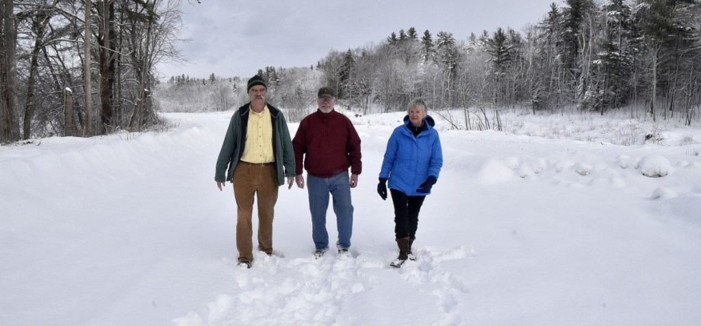 Morning Sentinel photo by David Leaming Members of the Somerset Woods Trustees, from left, Ernie Hilton, Jack Gibson and Nancy Williams, on Thursday walk on the Weston Homestead Farm property along the Kennebec River in Madison that the trust is acquiring and will make available to the public for recreation.