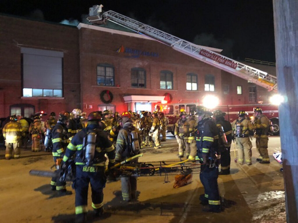 A ladder truck hoists firefighters to the roof of the Huhtamaki building on College Avenue in Waterville on Tuesday night. The road was closed off to accommodate equipment and firefighters responding to the fire alarm.