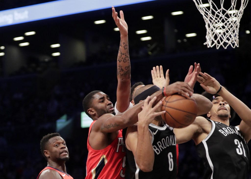 E'Twaun Moore of the Pelicans fights for control of the ball with Brooklyn's Jared Dudley during the first half Wednesday night in Brooklyn.