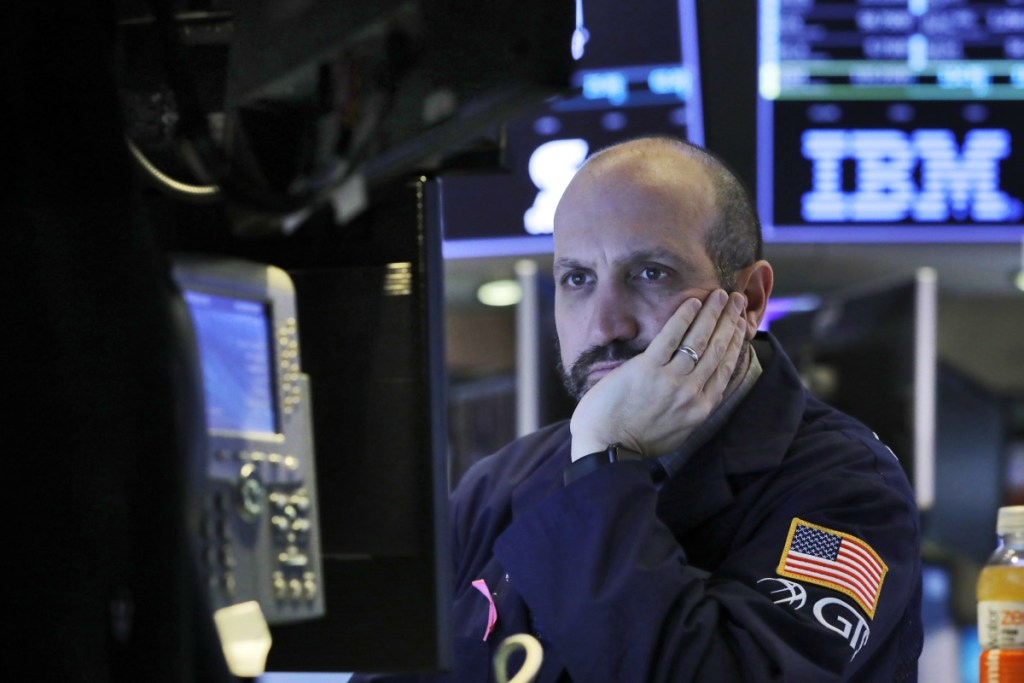 Specialist James Denaro works on the floor of the New York Stock Exchange on Thursday. Apple's shock warning that its Chinese sales are weakening ratcheted up concerns about the world's second-largest economy and weighed heavily on global stock markets as well as the dollar on Thursday.