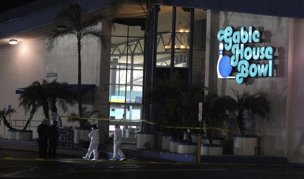 Police officers investigate a shooting at the Gable House Bowl in Torrance, Calif., on Saturday.  Police responded shortly after midnight to calls of shots fired at the bowling ally. Three people were killed and four were injured.