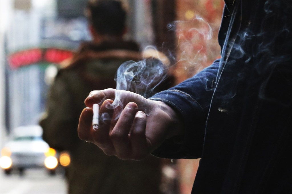 """Leyland Foster has a cigarette break in Post Alley, smoking a Camel Crush with a capsule in the filter that, when squeezed, releases menthol flavor. He's been smoking since he was 16, about 14 years. """"With coffee, oh yeah."""" (Alan Berner/Seattle Times/TNS)"""