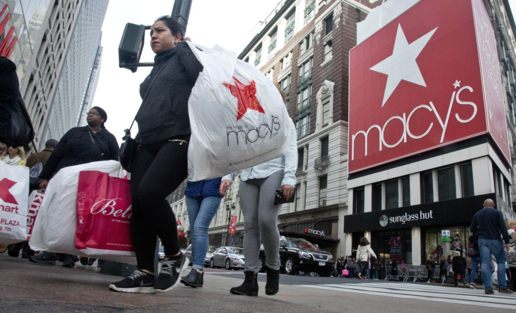 Shoppers cross a walkway near Macy's in New York. Macy's is considered a barometer of consumer spending, particularly for the nation's middle class.