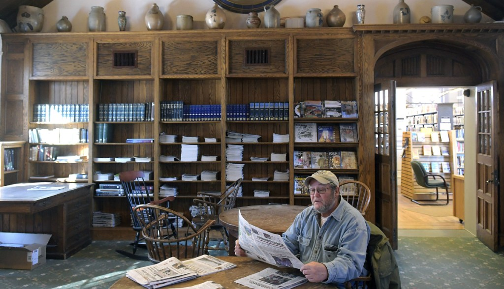 George Tatsak reads the newspaper Monday at the Gardiner Public Library. Gardiner officials proposed a new library fee schedule for partner communities based on the number of residents in each town. This comes after several years of concern by partner towns that the fees were too high and not predictable.