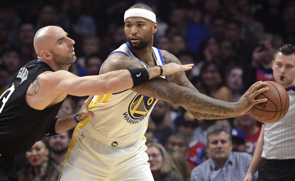 DeMarcus Cousins, right, posts up against Clippers center Marcin Gortat during Golden State's 112-94 win Friday night. Cousins made his debut with Golden State and scored 14 points to help the Warriors in their seventh straight victory.