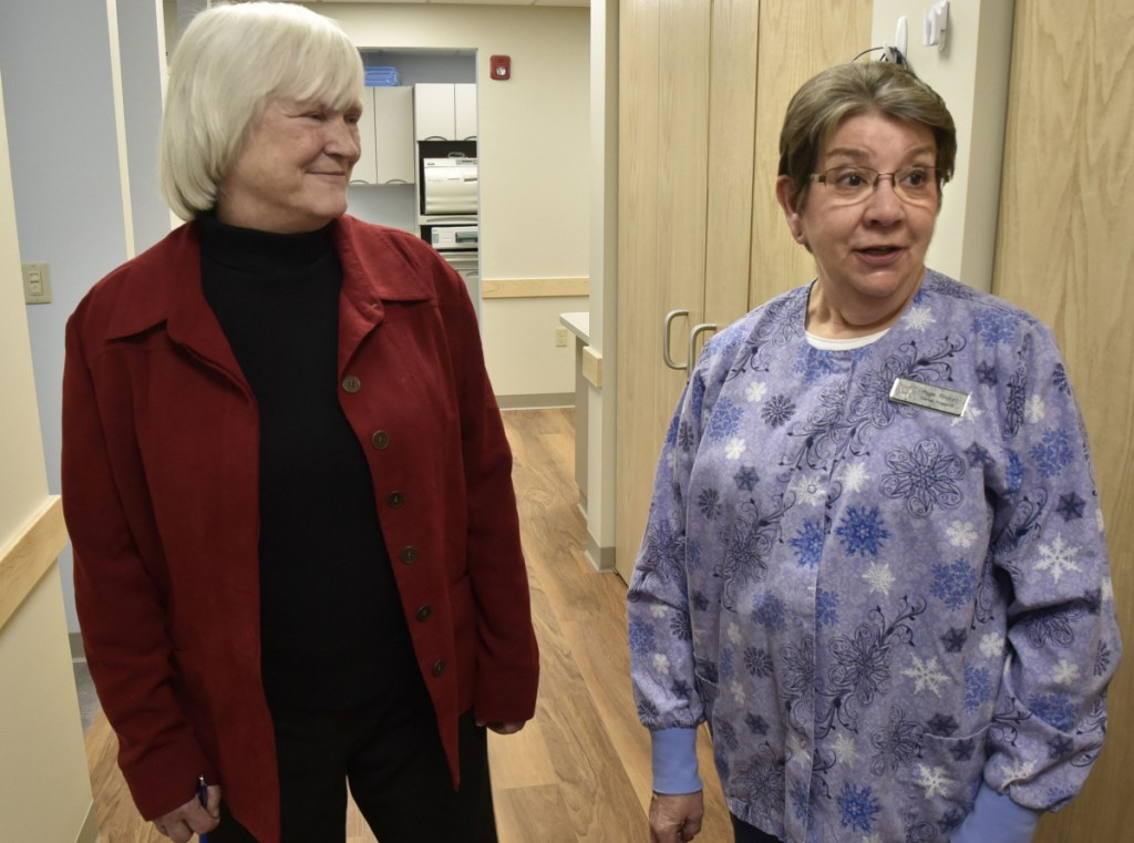Dr. Barbara Covey, left, chairman of the board of the Waterville Community Dental Center, listens as dental hygienist Hope Ricker points out the benefits of the new facility located in FirstPark in Oakland, including the larger space and more accessible parking.