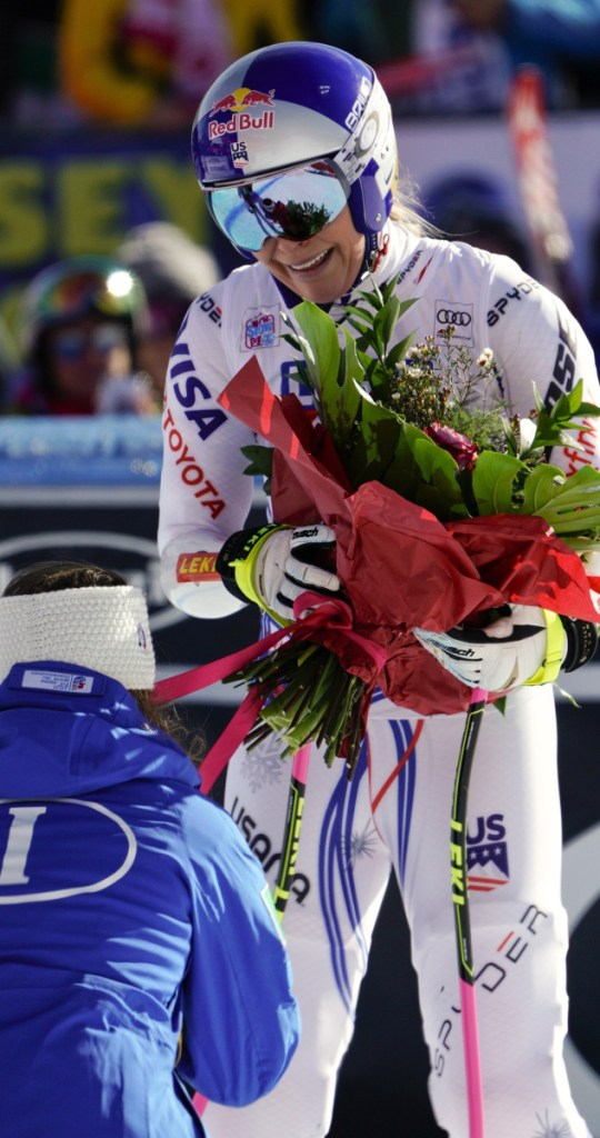 Lindsey Vonn, top, receives flowers from friend and rival Sofia Goggia of Italy after Sunday's World Cup super-G race in Cortina D'Ampezzo, Italy.