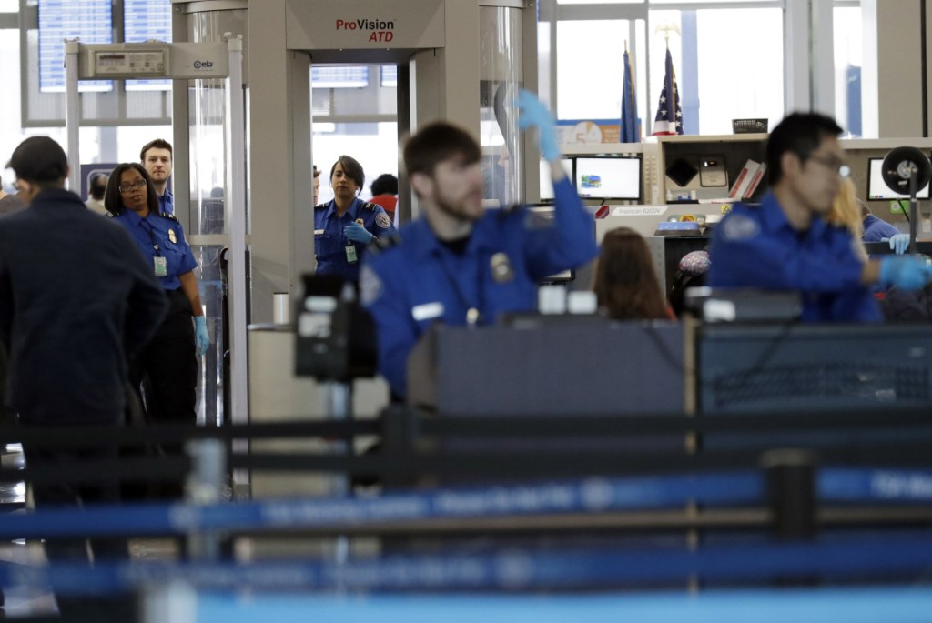 Transportation Security Administration officers work at a checkpoint at O'Hare airport in Chicago. The TSA said Sunday's absence rate of 10 percent compared to 3.1 percent on the same Sunday a year ago.