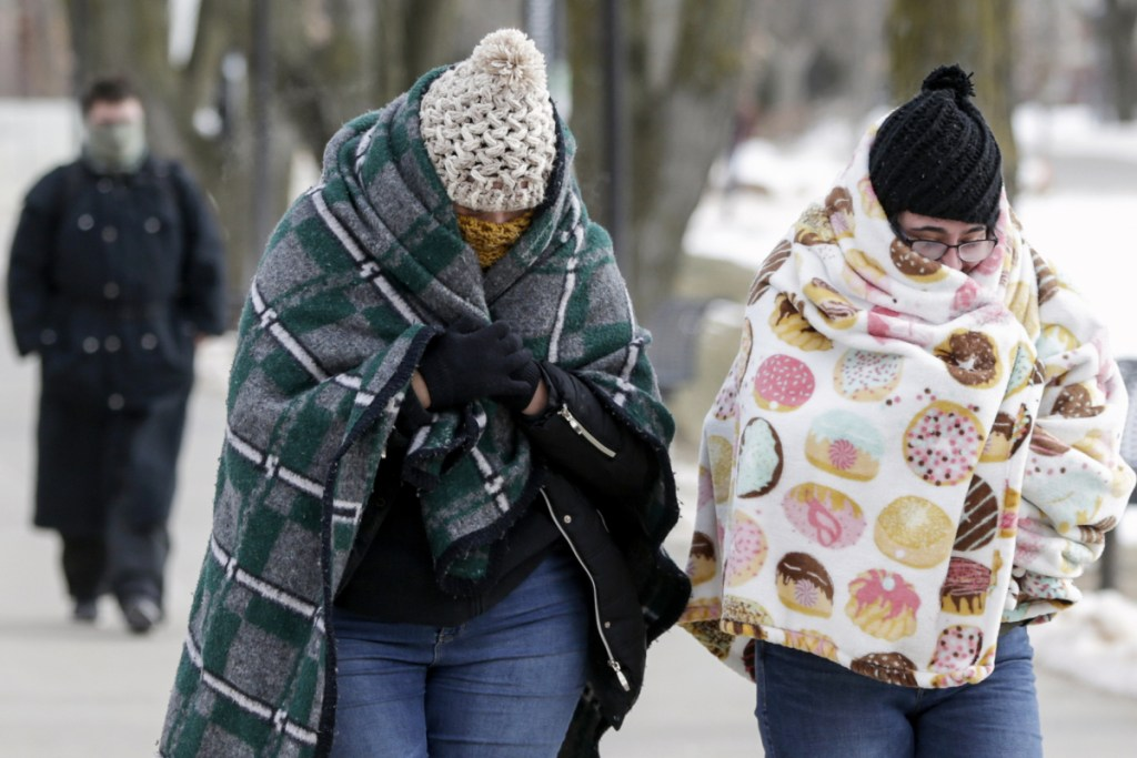 Pedestrians bundle up in sub-freezing temperatures on the campus of the University of Nebraska-Omaha, in Omaha, Nebraska, on Wednesday. A deadly arctic deep freeze enveloped the Midwest with record-breaking temperatures, triggering widespread closures of schools and businesses, and the canceling of more than 1,600 flights.