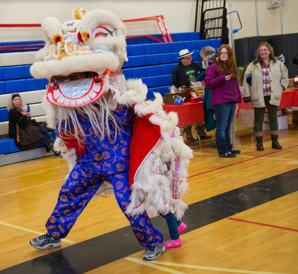 Participants perform the lion dance during a Chinese New Year celebration in the Westbrook Performing Arts Center on Saturday. The  lion is believed to chase away evil spirits and provide for a good year, according to one of the performers.