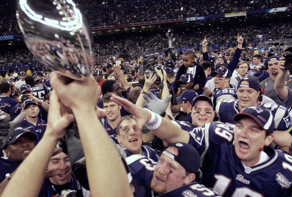 Lemme touch it: New England Patriots players reach out for the Vince Lombardi Trophy after their dramatic 20-17 victory over the St. Louis Rams in Super Bowl XXXVI in New Orleans on Feb. 3, 2002.