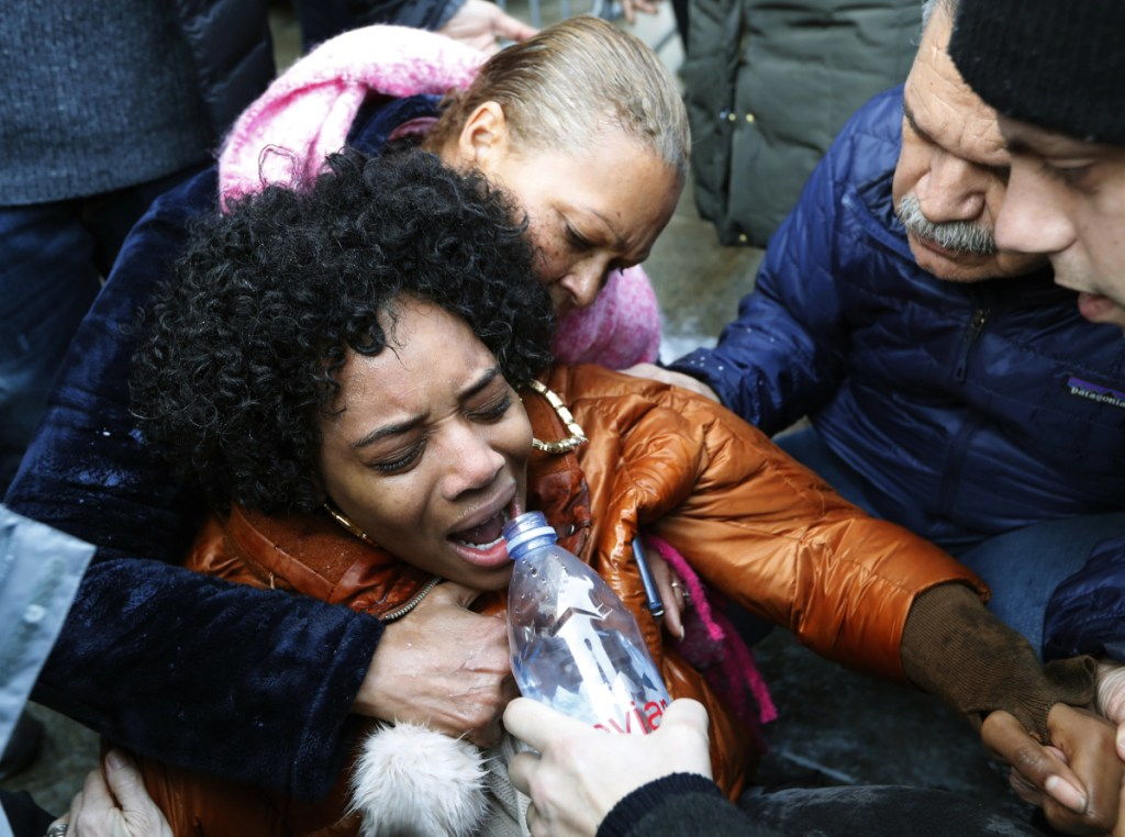 A woman is helped after guards used pepper spray when she and others stormed the entrance of the Metropolitan Detention Center in Brooklyn on Sunday.