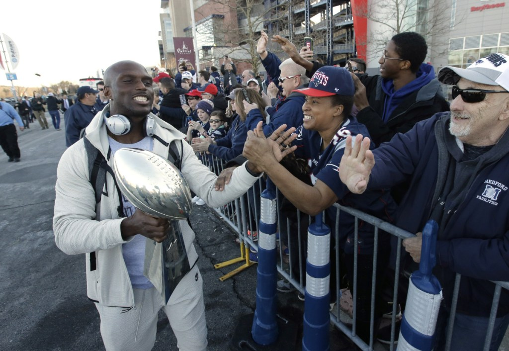 New England cornerback Jason McCourty, left, holds the Lombardi trophy as he greets fans following the team's arrival at Gillette Stadium on Monday.