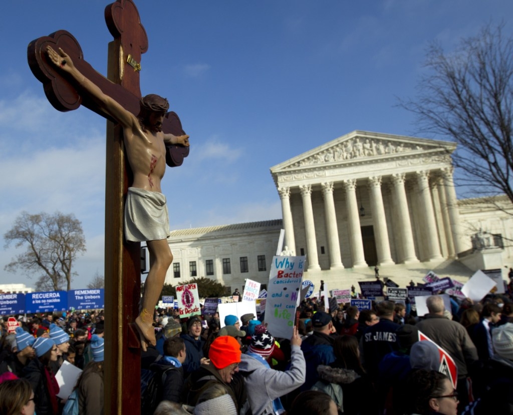 Anti-abortion activists march outside the U.S. Supreme Court last month. Activists on both sides of the abortion debate reacted cautiously to a Supreme Court vote blocking Louisiana from enforcing new abortion regulations.