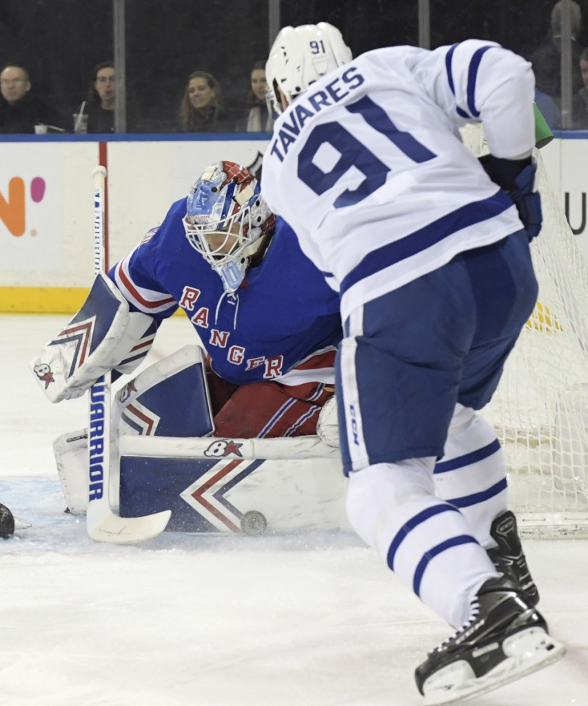 Rangers goaltender Alexandar Georgiev makes one of his 55 saves on a shot by Toronto's John Tavares in the first period Sunday night at New York.