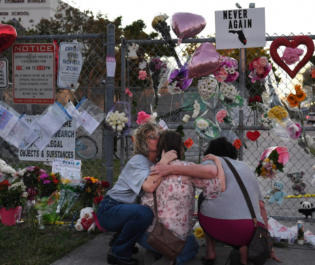 People grieve last February after a shooting at a Florida high school left 17 dead. Some students will do service work Thursday to observe the anniversary. Washington Post/Matt McClain