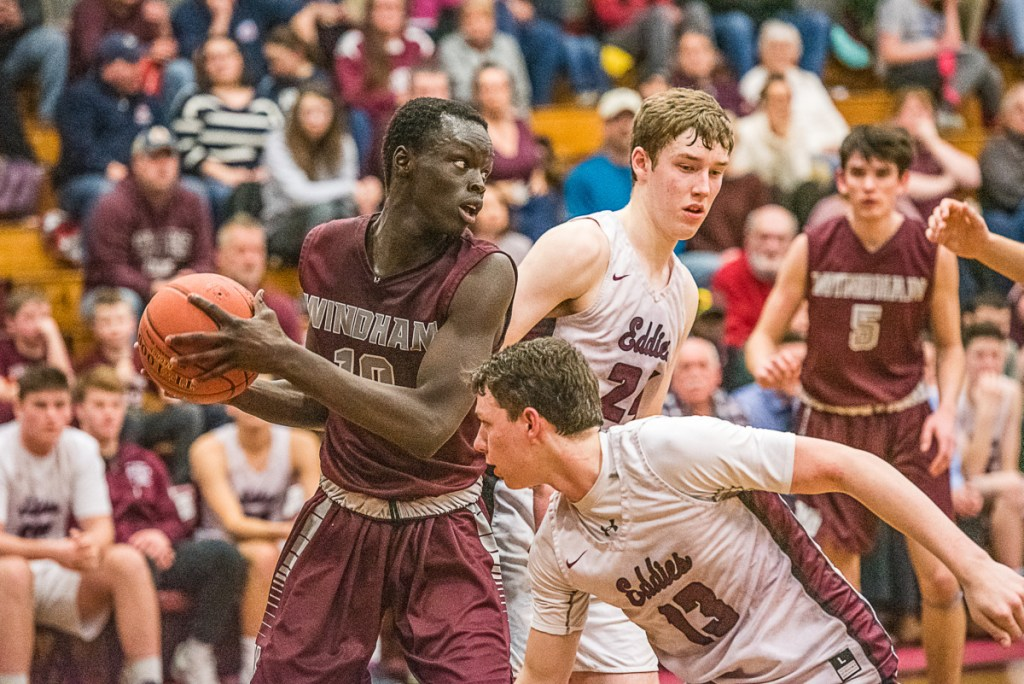 Dierhow Bol of Windham looks for an open teammate while defended by Edward Little's Cam Yorke, front, during their Class AA North quarterfinal Wednesday in Auburn. Edward Little won, 45-34.