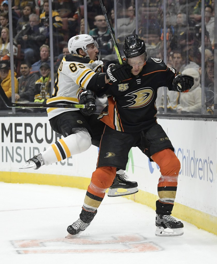 Bruins left wing Brad Marchand collides with Anaheim defenseman Hampus Lindholm.