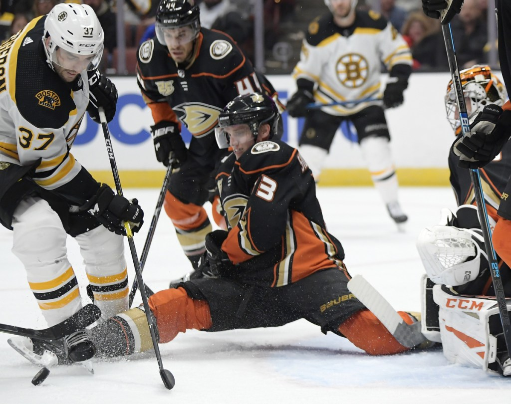 Anaheim right wing Jakob Silfverberg tries to stop a shot by Boston center Patrice Bergeron during the third period Friday night. The Bruins won 3-0.