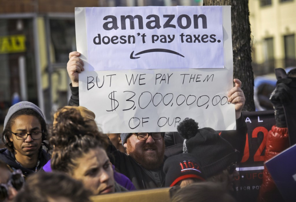Protesters hold up anti-Amazon signs during a coalition rally and press conference of elected officials, community organizations and unions opposing Amazon headquarters getting subsidies to locate in Long Island City, in New York, on Nov. 14. Local resistance to the online retailer building part of its headquarters in Long Island City was almost immediate. The deal dissolved on Thursday.