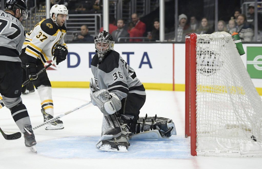Boston center Patrice Bergeron scores on Kings goaltender Jack Campbell as center Jeff Carter watches during the third period in Los Angeles. The Bruins won 4-2.