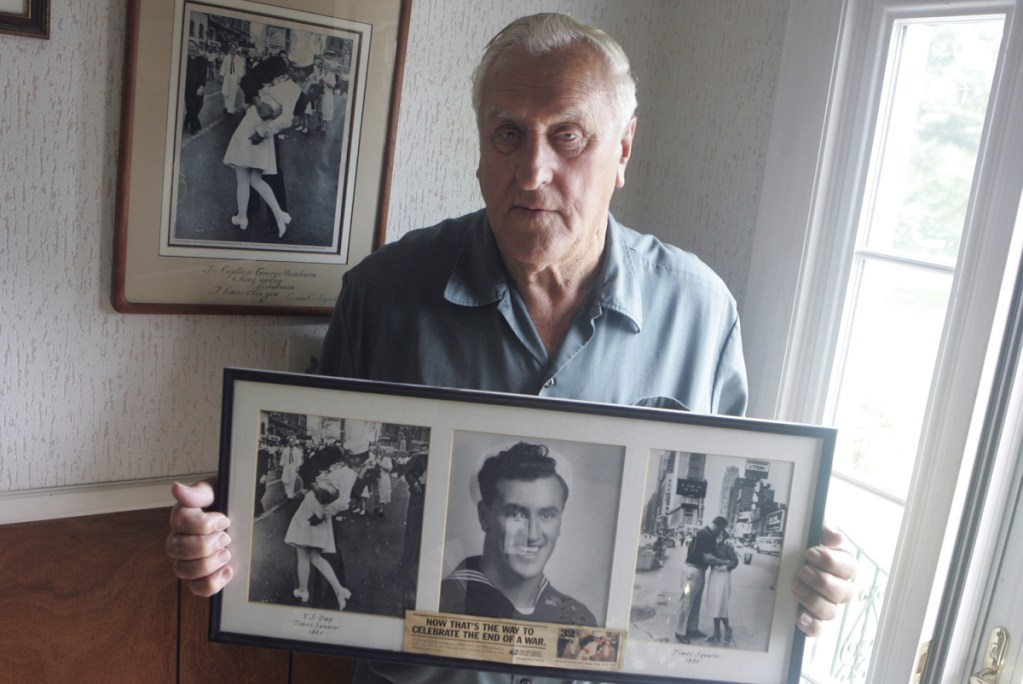 George Mendonsa is shown in 2009 in Middletown, R.I., holding a copy of the famous Alfred Eisenstadt photo of Mendonsa kissing a woman in a nurse's uniform in Times Square on Aug. 14, 1945, while celebrating the end of World War II.