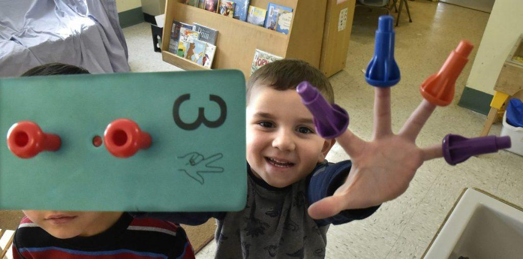 A boy shows off his fingers while playing with a puzzle at the Sweatt-Winter Child Care and Early Education Center on Tuesday morning. The on-campus program will be moving into another nearby building in Farmington by the end of summer.