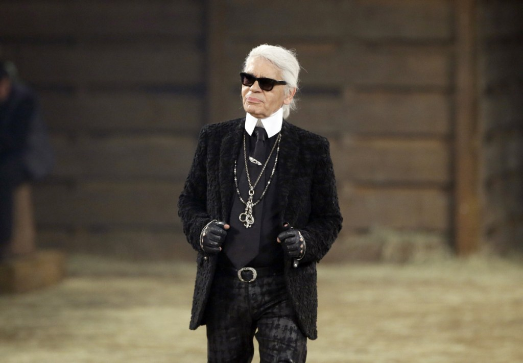 In this 2013 file photo, Chanel designer Karl Lagerfeld takes a bow at the end of his Metiers d'Art fashion show in Dallas. Chanel's iconic couturier, Lagerfeld, whose accomplished designs as well as trademark white ponytail, high starched collars and dark enigmatic glasses dominated high fashion for the last 50 years, has died. He was around 85 years old.