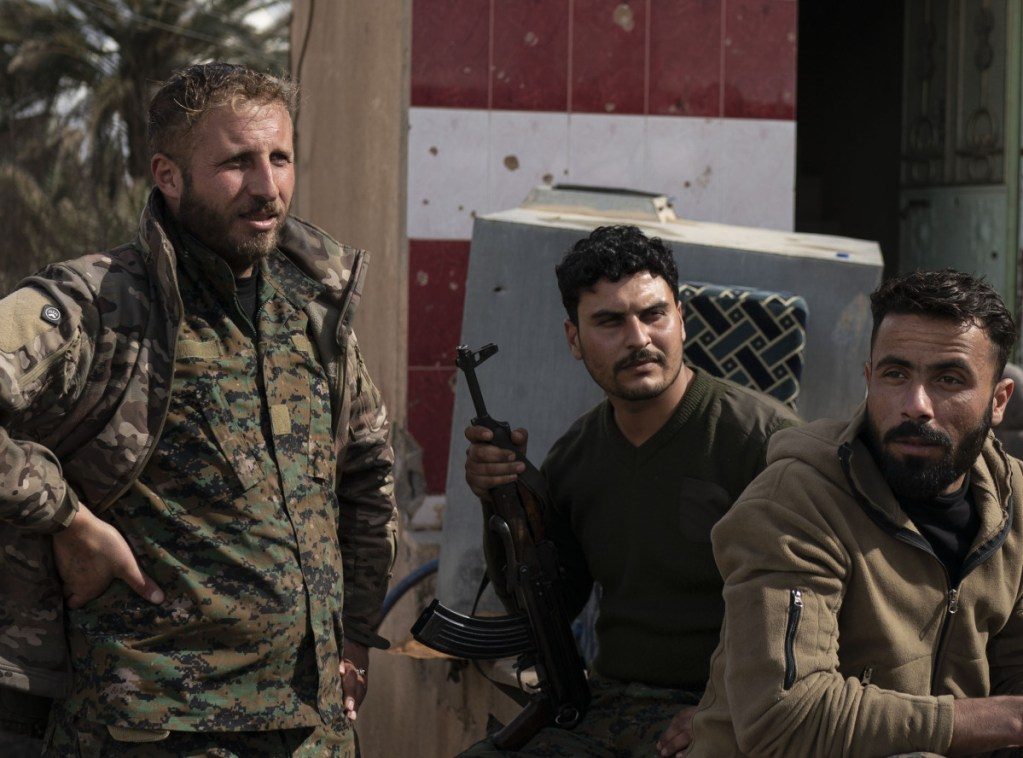 U.S.-backed Syrian Democratic Forces fighters wait outside a temporary base near the last land still held by Islamic State militants in Baghouz, Syria, Monday.
