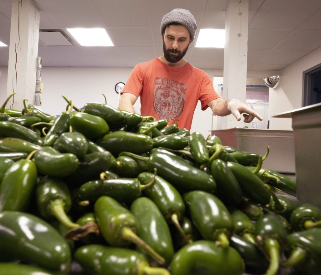 Henry Ginsberg stems jalapeño peppers for Spruced Up hot sauce.