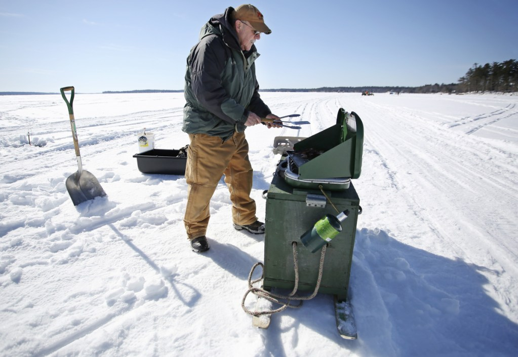 Jim Nagle of Connecticut has his grill mounted on a wooden chest, which attached to an old pair of skis and made for an easy transport at the Sebago Lake Rotary Ice Fishing Derby.