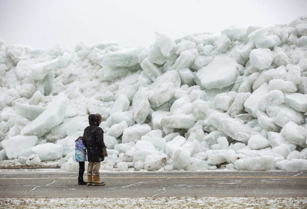 Local residents check out a massive buildup of ice that was pushed onto the shore of Mather Park in Fort Erie, Ontario, Canada, on Monday. A wind storm Sunday broke an ice boom in Lake Erie and allowed the ice, which was floating on the water at the mouth of the Niagara River, to spill over the retaining wall and onto the shore and the roadway above.