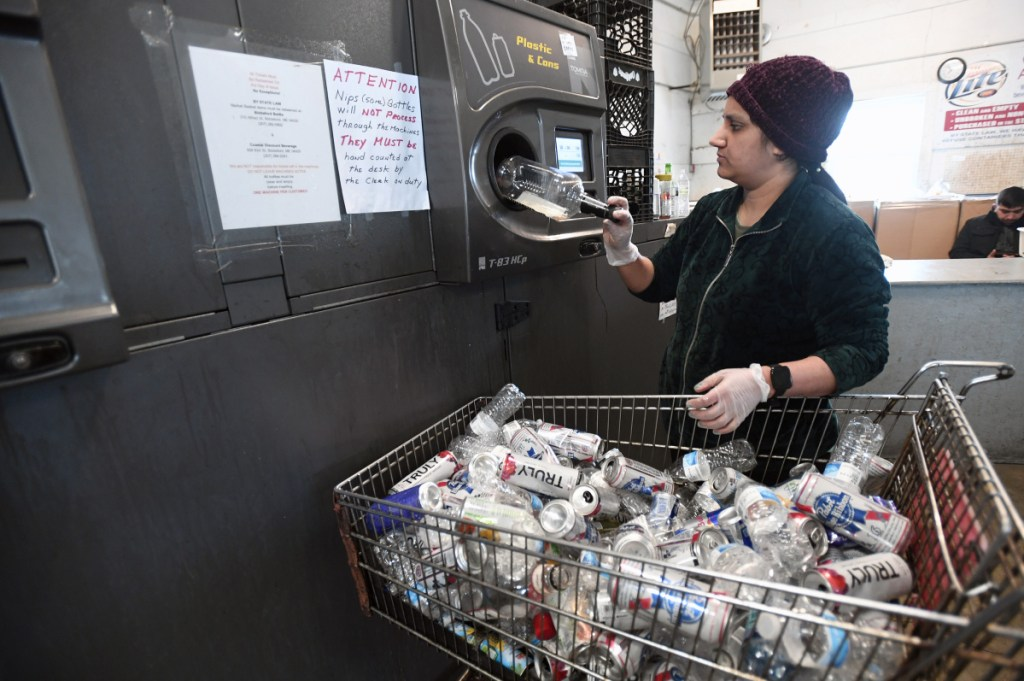 Pooja Paten, an employee of Madden Beverage and Redemption Center in Saco, loads returnables into a reverse vending machine at the redemption center Wednesday.